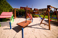 Children s play area well designed with slide trampoline and swing surrounded by trees Stock Image