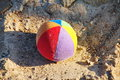 Children's soft fabric and striped multi-colored ball about the yellow quartz sand of the bright sun. Royalty Free Stock Photo