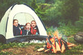 Children`s tourism. Happy kids girls in campaign in tent near f