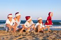 Children in santa claus hat are sitting on beach happy outdoor Stock Images