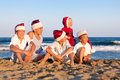 Children in santa claus hat are sitting on beach happy outdoor Royalty Free Stock Photo