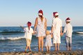 Children in santa claus hat are standing on beach happy outdoor Royalty Free Stock Photo