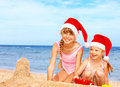 Children in santa hat playing on  beach. Royalty Free Stock Photography