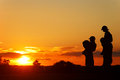 Children on the shoulders of parents go summer evening silhouettes sunset Royalty Free Stock Photo