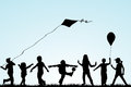 Children silhouettes playing in the park with kite Royalty Free Stock Photo