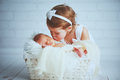 Children sister kisses brother  newborn sleepy  baby on a light Royalty Free Stock Photo