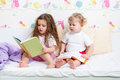 Children sisters read book in bed kids reading a Stock Photography
