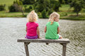 Children sitting on the bench two blond girl Royalty Free Stock Image