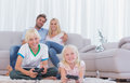 Children sitting on the carpet playing video games Royalty Free Stock Photo