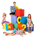 Children sitting at cube and holding figure Royalty Free Stock Images