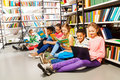Children sitting on floor in library and studying Royalty Free Stock Photo