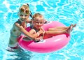 Children sitting on inflatable ring in swimming pool Royalty Free Stock Photography