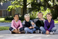 Children sitting in a row outdoors Royalty Free Stock Photos