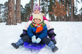 Children on sleds in snow cute sister and brother forest focus the boy Royalty Free Stock Photo