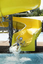 Children slide down a water slide sunny day Royalty Free Stock Photo