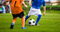 Children Soccer Football Players. Footballers Kicking Football Match Game on the Grass Royalty Free Stock Photo
