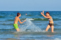 Children splashing at the sea in summer day Royalty Free Stock Photos