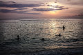 Children swim in the ocean evening sunset Royalty Free Stock Photo