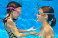 Children swim in pool underwater, girls in goggles have fun Royalty Free Stock Photo