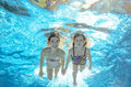 Children swim in pool underwater, girls have fun in water Royalty Free Stock Photo