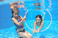 Children swim in pool underwater, happy active girls have fun under water, kids sport