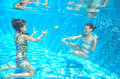 Children swim in pool underwater, happy active girls have fun under water, kids sport Royalty Free Stock Photo