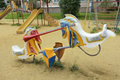 Children swing in the form of horses. Playground.
