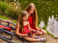 Children with tablet pc near bicycle into river in park . Royalty Free Stock Photo