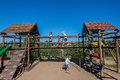 Children three playground pr school childrens with slides ramps ropes webbing walkway and swings with small wood roof coverings on Royalty Free Stock Image