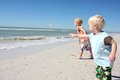 Children throwing seashells into the ocean two a young boy and his baby brother are standing on beach Royalty Free Stock Image