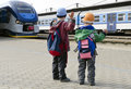 Children at train station two with backpacks waving to trains back view Stock Images