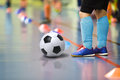 Children training soccer futsal indoor gym. Young boy with soccer ball training indoor football. Little player in light blue sport Royalty Free Stock Photo