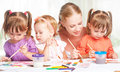 Children twin sisters draw paints with her mother in kindergarten little Royalty Free Stock Photos