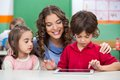 Children using digital tablet with teacher at classroom desk Royalty Free Stock Photography