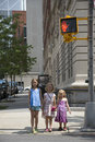 Children wait to cross street at stop signal Royalty Free Stock Photo