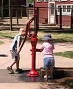 Children at Water Pump Royalty Free Stock Photo