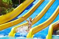 Children on water slide at aquapark summer holiday Stock Photos