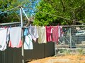 Children Wet clothes hanging on a backyard washing line in the sundry. Royalty Free Stock Photo
