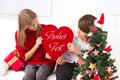 Children wish you merry christmas with heart decoration with sign Stock Photos