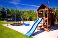 Children x s play area well designed with blue slide trampoline and swing surrounded by trees and grass blue sky background Stock Image