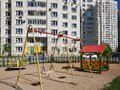 children& x27;s playground with swings in courtyard of residential building in the city, Russia Royalty Free Stock Photo