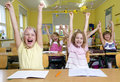 Children in a yellow classroom they all raises up the hands Royalty Free Stock Photo