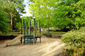 Childrens empty playground in the park middle of a sand pit with a bench and surrounded by trees and scrubs Stock Photos