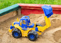Childrens excavator children s toy tractor in sandbox Royalty Free Stock Photo