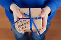 Childrens hands holding a gift or present box with kraft paper and tied blue ribbon tag on Happy fathers day Royalty Free Stock Photo