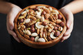 Childrens hands holding a wooden bowl with mixed nuts. Healthy food and snack. Walnut, pistachios, almonds, hazelnuts and cashews. Royalty Free Stock Photo