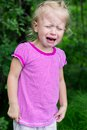 Childrens hysterics little girl crying heavily on green background Royalty Free Stock Photo
