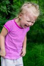 Childrens hysterics little girl crying heavily on green background Stock Images