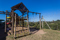 Childrens playground pr school with slides ramps ropes webbing walkway and swings with small wood roof coverings on walkway venue Royalty Free Stock Photo