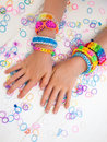 Childs arms wearing multicoloured bracelets colourful elastic loom band worn on a child hands against a white table top Stock Photo